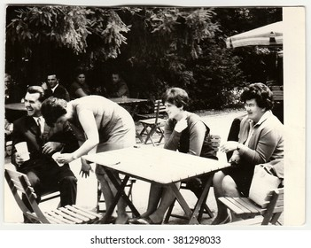 THE CZECHOSLOVAK SOCIALIST REPUBLIC - CIRCA 1960s: Vintage photo shows group of people sit at the garden restaurant.