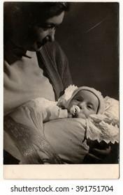 THE CZECHOSLOVAK SOCIALIST REPUBLIC - CIRCA 1960s: Vintage photo shows mother cradles her baby. Black & white antique photo.