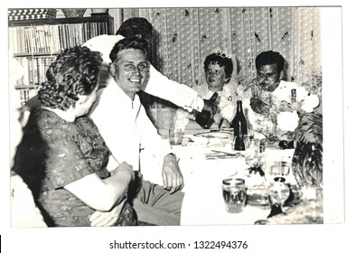 THE CZECHOSLOVAK SOCIALIST REPUBLIC - CIRCA 1970s: Vintage photo shows newlyweds and wedding guests sitting at wedding table. Retro black and white photography.