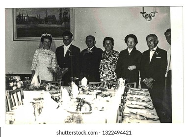 THE CZECHOSLOVAK SOCIALIST REPUBLIC - CIRCA 1970s: Vintage photo shows newlyweds and wedding guests posing at wedding table. Retro black and white photography.