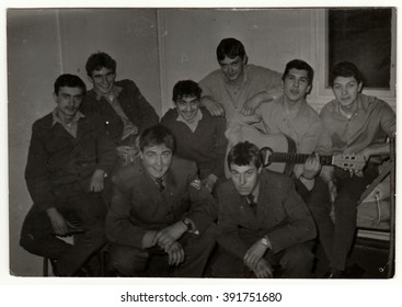 THE CZECHOSLOVAK SOCIALIST REPUBLIC - CIRCA 1970s: Vintage photo shows soldiers pose in barracks. One of them plays the guitar. Black & white antique photo.