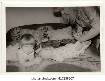 THE CZECHOSLOVAK SOCIALIST REPUBLIC - CIRCA 1970s: Retro photo shows mother puts on the baby. Black & white vintage photography.