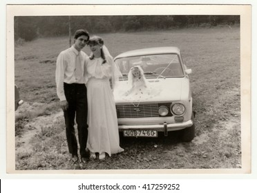 THE CZECHOSLOVAK SOCIALIST REPUBLIC - CIRCA 1970s: Retro photo shows newlyweds and wedding car. Black & white vintage photography.