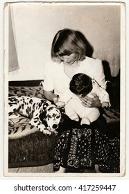 THE CZECHOSLOVAK SOCIALIST REPUBLIC - CIRCA 1970s: Retro photo shows child, mother and dog who sit on sofa. Black & white vintage photography.