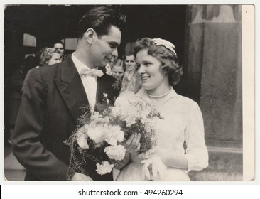 THE CZECHOSLOVAK SOCIALIST REPUBLIC - CIRCA 1970s: Vintage photo shows newlyweds in front of church. Bride holds a bunch of flowers (white carnations). Retro black & white  photography