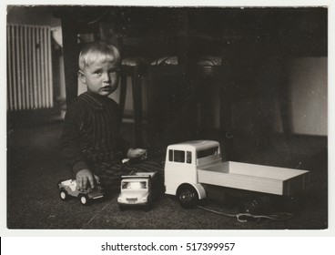 THE CZECHOSLOVAK SOCIALIST REPUBLIC - CIRCA 1970s: Vintage photo shows a small boy plays with toy cars in the living room. Funny photography of a cute boy. Retro black & white  photography.