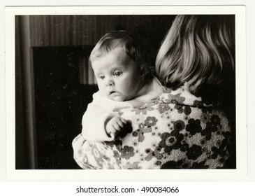 THE CZECHOSLOVAK SOCIALIST REPUBLIC - CIRCA 1980s: Vintage photo shows mother cradles baby. Retro black & white  photography.
