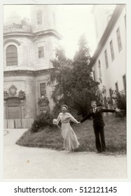 THE CZECHOSLOVAK SOCIALIST REPUBLIC - CIRCA 1980s: Vintage photo shows young newly-weds (bridal couple) in front of church. Retro black & white  photography.