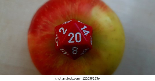 D20 red dice with an apple in the background