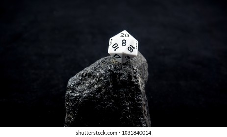 a d20 stands atop a mountain of coal having conquered it