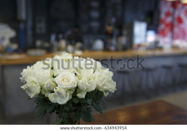 "Da Lat town, Vietnam - April 30, 2017 :  Pot white roses on a background of a wooden table in the cafe lighting view. at the ""La Viet"" cafe in Da Lat town, Vietnam"