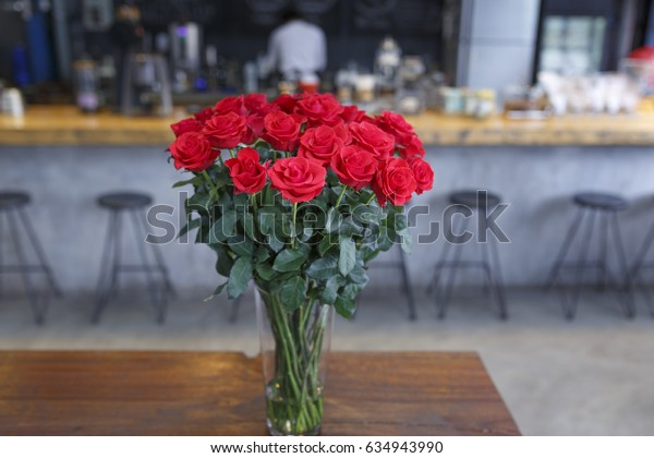 "Da Lat town, Vietnam - April 29, 2017 :  Pot red roses on a background of a wooden table in the cafe lighting view. at the ""La Viet"" cafe in Da Lat town, Vietnam"
