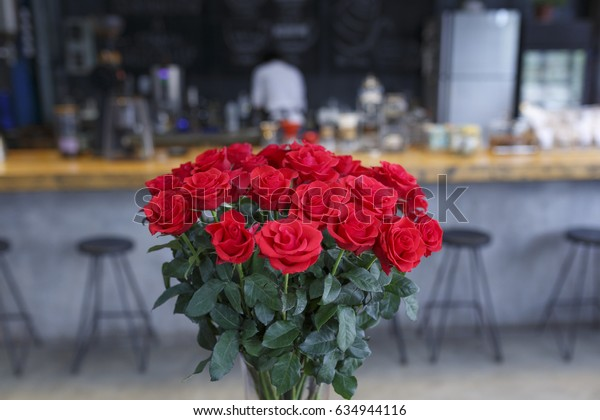 """Da Lat town, Vietnam - April 29, 2017 :  Pot red roses on a background of a wooden table in the cafe lighting view. at the """"La Viet"""" cafe in Da Lat town, Vietnam"""