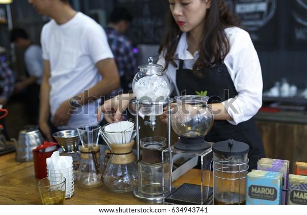 "Da Lat town,Vietnam - April 29 ,2017 :  Barista making coffee. Professional coffee staff doing their work at the ""La Viet"" cafe in Da Lat town, Vietnam"