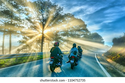 Da Lat, Vietnam - May 13, 2018: Motorcyclists driving on road through pine forests with the rays of the sun shining on the misty beautiful road, this is a beautiful road on the Da Lat plateau, Vietnam