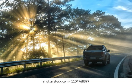 Da Lat, Vietnam - May 13, 2018: Cars driving on the country asphalt road through pine forests with rays shining on the foggy beautiful road, this is a beautiful road on the Da Lat plateau, Vietnam.