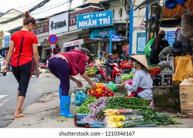 DA LAT, VIETNAM - SEPTEMBER 20: A Vietnamese woman buys paprika on the street on September 20, 2018 in Da Lat, Vietnam.