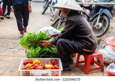 DA LAT, VIETNAM - SEPTEMBER 23: A senior woman sells greens and paprika on the street on September 23, 2018 in Da Lat, Vietnam.