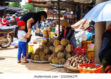 DA LAT, VIETNAM - SEPTEMBER 23: A Vietnamese woman with a child buys durian on the street market on September 23, 2018 in Da Lat, Vietnam.