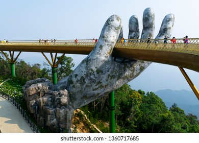 Da Nang, Vietnam - Mar. 29, 2019: The Golden Bridge. The two giant colossal hands emerging from the mountains holding up the golden bridge at the height of 1,414 m from the sea level in Ba Na Hills.