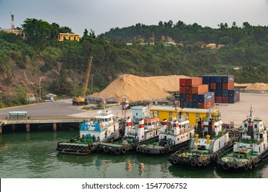 Da Nang, Vietnam - March 9, 2019: Tien Sa Port in Da Nang Bay. Five tugboats anchored in dock with blue and red container boxes, a huge pile of yellow sand and green forested hills in back.