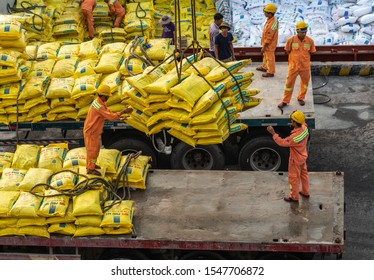 Da Nang, Vietnam - March 9, 2019: Tien Sa Port in Da Nang Bay. Closeup of men in orange garb manually guiding suspended load of yellow bags onto bed of truck.