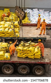Da Nang, Vietnam - March 9, 2019: Tien Sa Port in Da Nang Bay. Closeup of men in orange garb manually uncoupling suspended load of yellow bags onto bed of truck.