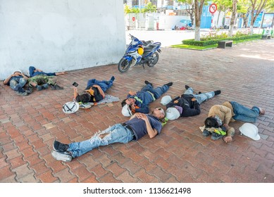 Da Nang, Vietnam - May 7, 2018: Group of workers relax and sleep, having their shoes and construction helmets off, in the shadow of a bridge in Bach Dang Street.