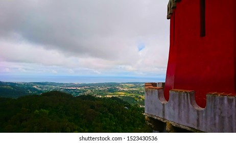 Palácio da Pena, Lisbon, Portgual - June 3, 2018: exterior of Pena Palace with red wall and tower overseeing mountains and cityscape under cloudy sky