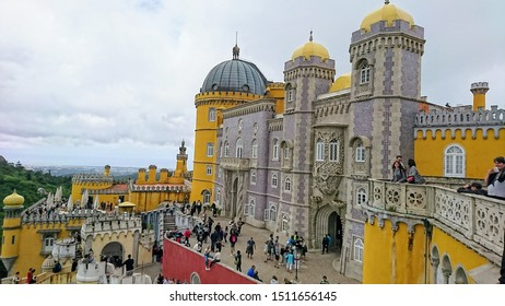 Palácio da Pena, Sintra, Portugal - June 3, 2018: Pena Palace: view from balcony to colorful royal palace with purple and yellow wall while tourists were visiting under a cloudy sky