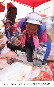 Da Shan Bao, China - February 1, 2016: Woman selling sugar in a local market in China