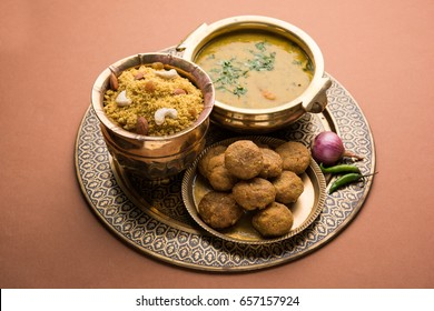 Daal Baati Churma is a popular Healthy food from Rajasthan, India. Served antique Brass plate and bowl over moody background.