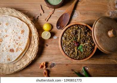 Daal Makhni with traditional wheat bread and sauce in traditional wooden bowl