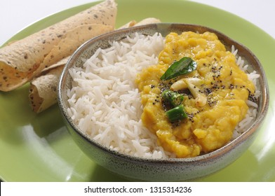 Daal rice, yellow daal, Toor daal in a bowl with roasted papad