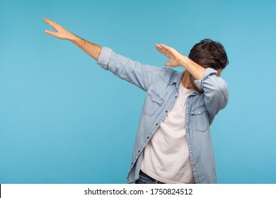 Dab dance. Portrait of man in denim shirt making dabbing movement, famous internet meme of success victory, expressing happiness and following trends. indoor studio shot isolated on blue background