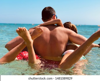 Dab with son and daughter are swimming. Summertime on the beach, happy family fun on the water.