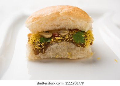 Dabeli is an Indian snack item served with Pomegranate Seeds and Cilantro in white ceramic plate. It's a popular Navratri Festival food