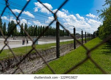 Dachau, Germany  - June 3, 2018: Visitors walk along the wire fence of the Dachau Concentration Camp near Munich