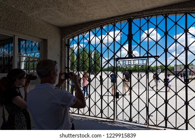 Dachau, Germany  - June 3, 2018: Two visitors photograph the entrance gate of the Dachau Concentration Camp near Munich