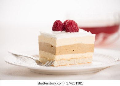 Dacquoise cake of Bavarian cream, coffee-flavored hazelnut praline, and almond meringue, topped with whipped cream. Garnished with raspberry and served with a cup of tea.
