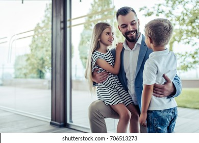 Dad arrives home from work, his little son and daughter are meeting him. Happy handsome man is kneeling, smiling and hugging his children.