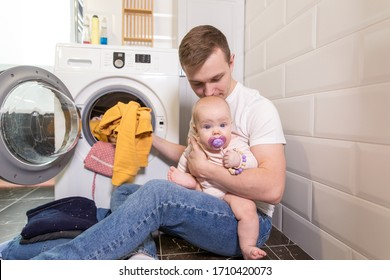 Dad with a baby in his arms sitting at home in the Laundry, washing things in the washing machine