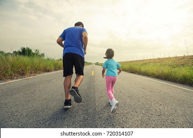 Dad and baby jogging in the street in the morning.