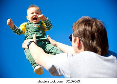 dad and baby son having fan outdoors