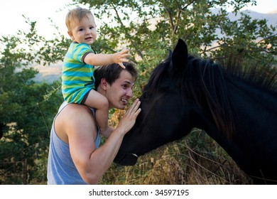 dad and baby son stroking beautiful black horse