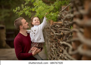Dad in a burgundy sweater admires his little daughter who sits in his arms