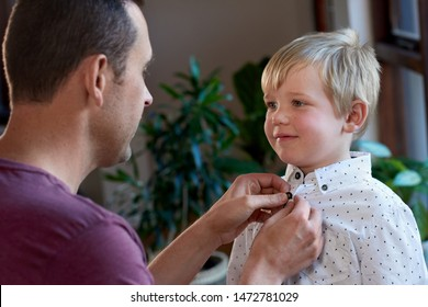 Dad buttoning up son's shirt, man to man talk father to son chat while getting dressed