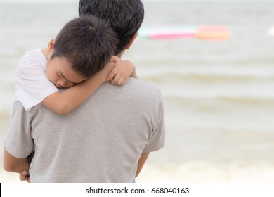 Dad carrying his son to sleep after strolling on the beach in summer