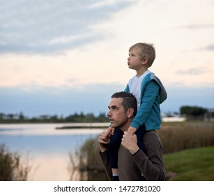 Dad carrying son on his shoulders, outdoor family time by the lake nature