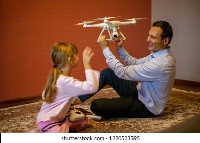 Dad with a child control copter. Dad teaches a child how to control a copter. Dad gave the child a gift copter.